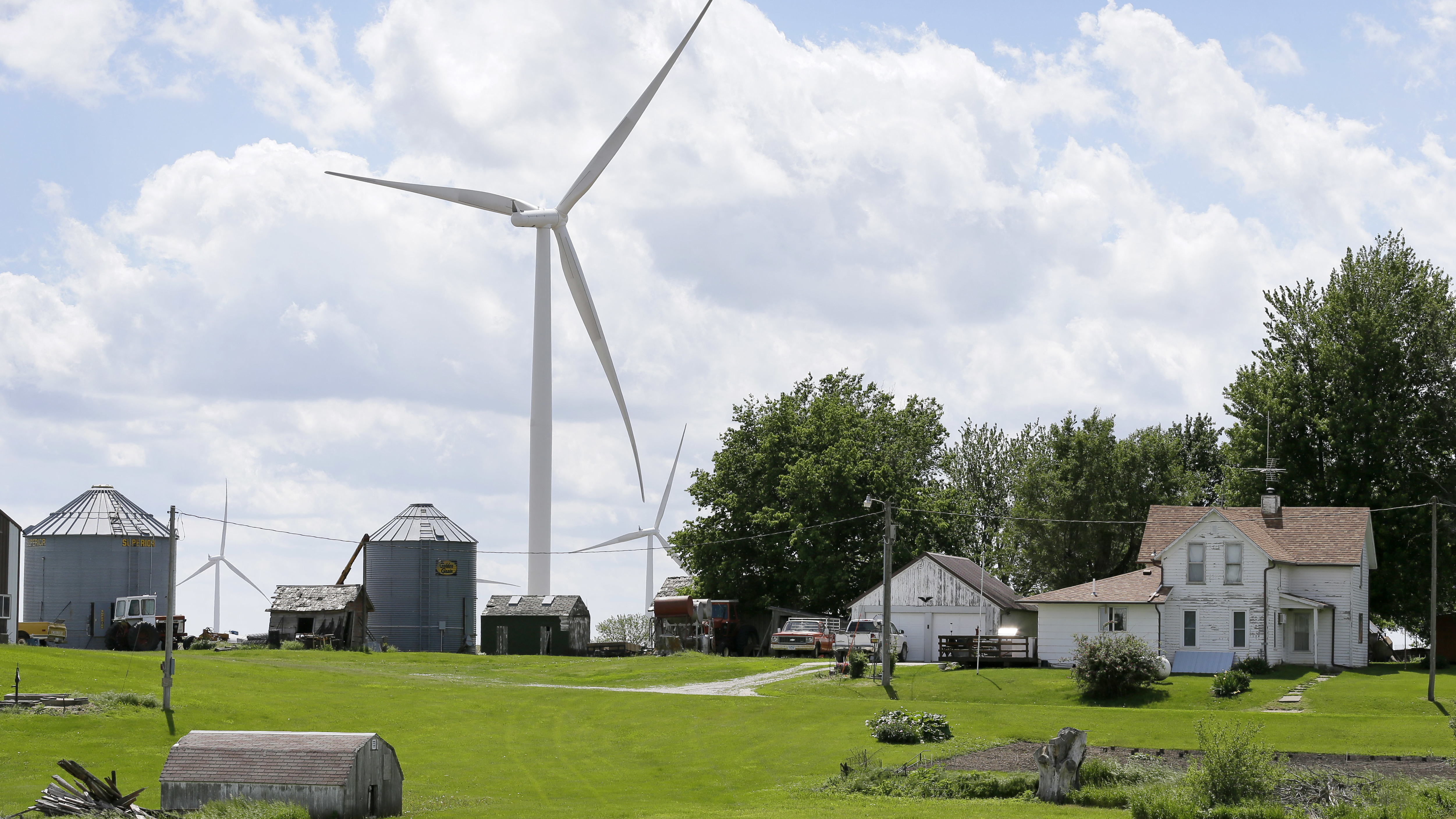 A wind turbine stands over a farmhouse in Adair, Iowa. Charlie Neibergall/AP