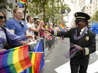 San Francisco Fire Department Deputy Chief Raemona Williams (right) passes out beaded necklaces to the crowd during the 2015 San Francisco Gay Pride Parade. Tony Avelar/AP