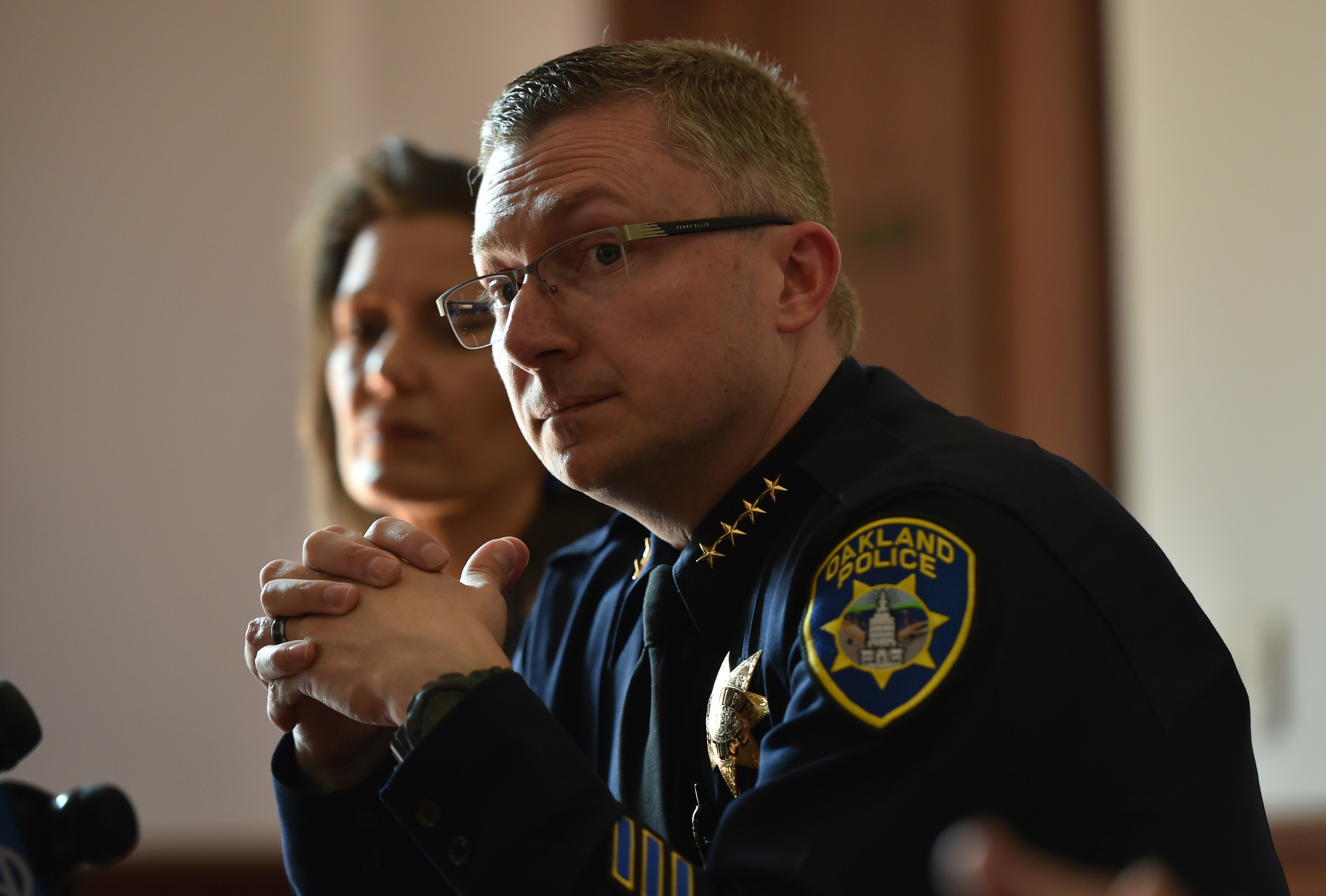 Oakland Police Chief Sean Whent, with Mayor Libby Schaaf behind him, listens to questions from the media on May 2, 2015, after May Day protests in Oakland, Calif. Whent has since resigned as police chief — as did two interim chiefs after him, over the course of a little more than a week. Josh Edelson/AFP/Getty Images