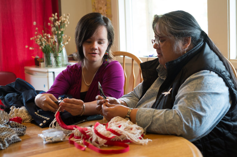 Lily Hope and Deanne Lampe attach silver cones to Chilkat fringe for their piece in the Sealaska Heritage Institute Native Fashion Show. (Photo by Annie Bartholomew/KTOO)