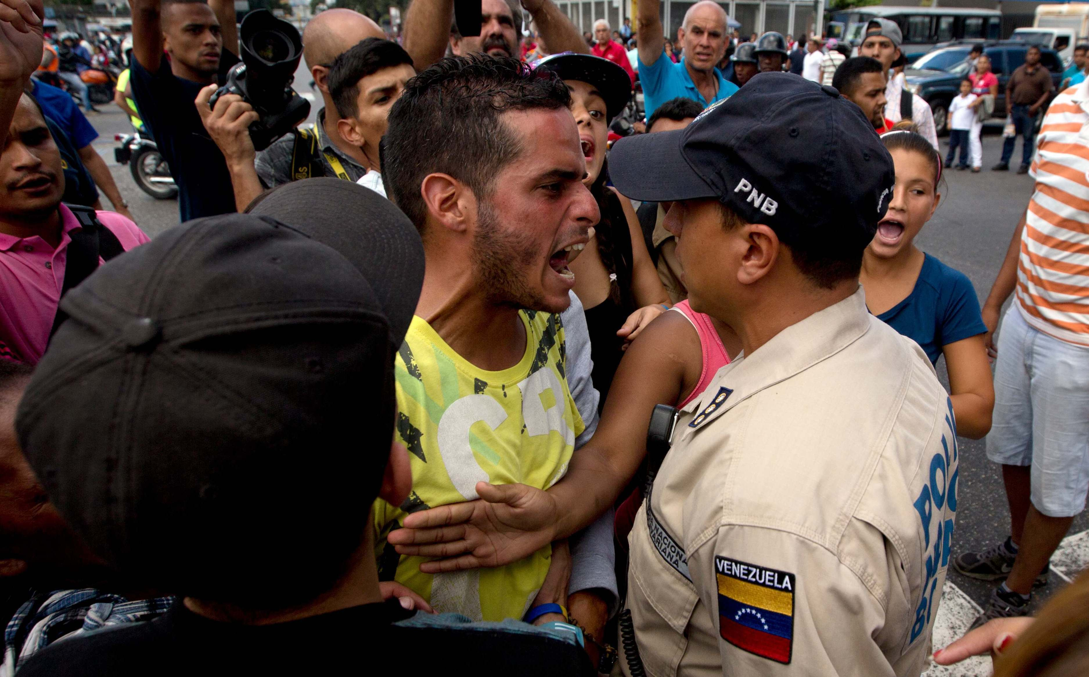 An angry man outside a grocery store argues with a policeman in Caracus, Venezuela, on June 8 amid the country's ongoing food shortages. After waiting for hours, customers began protesting, an increasingly common occurence in Venezuela, which is suffering a severe economic crisis. Fernando Llano/AP