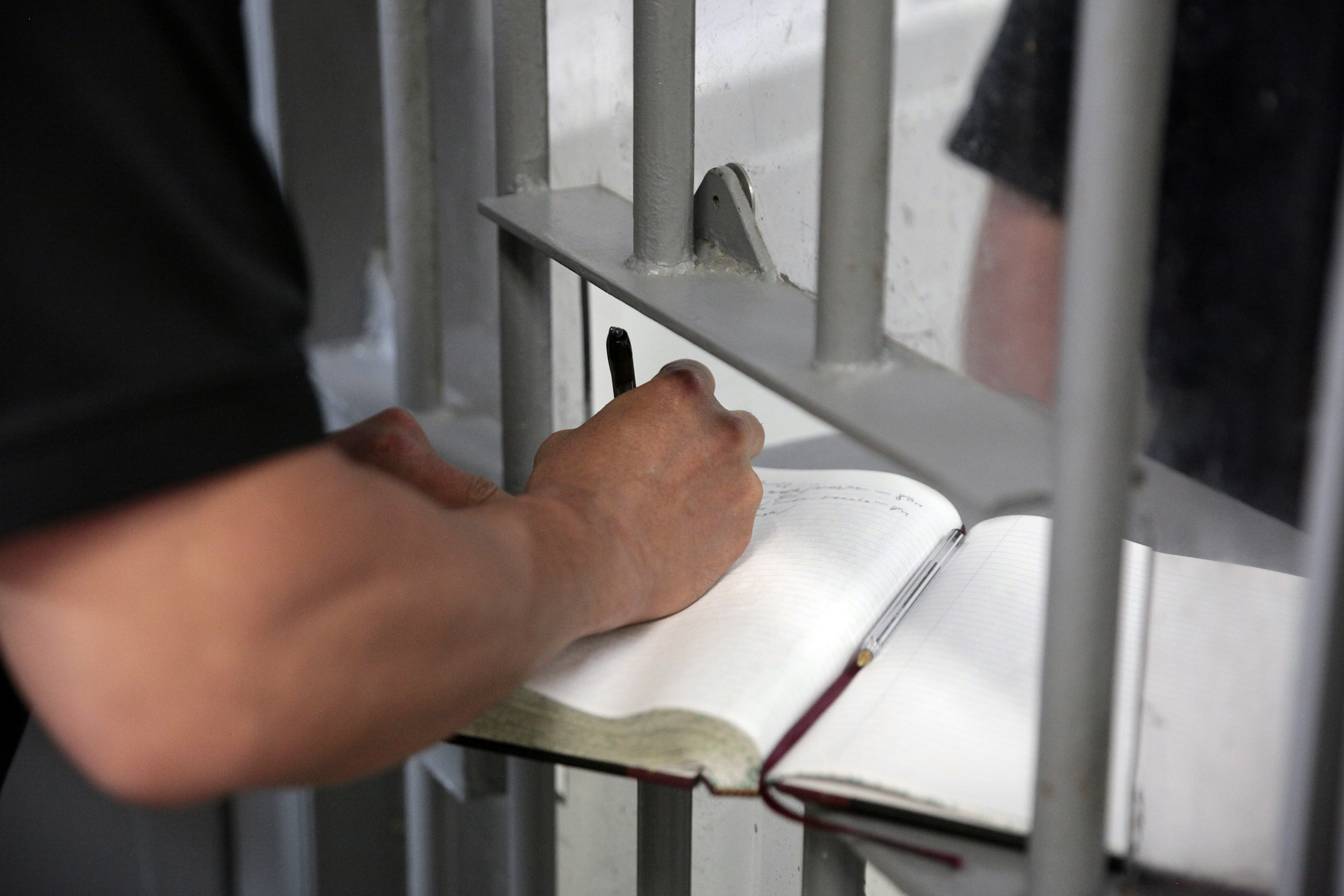 A guard signs several visitors from KTOO in at the Lemon Creek Correctional Center on June 18, 2016, in Juneau, Alaska. (Photo by Rashah McChesney/KTOO)