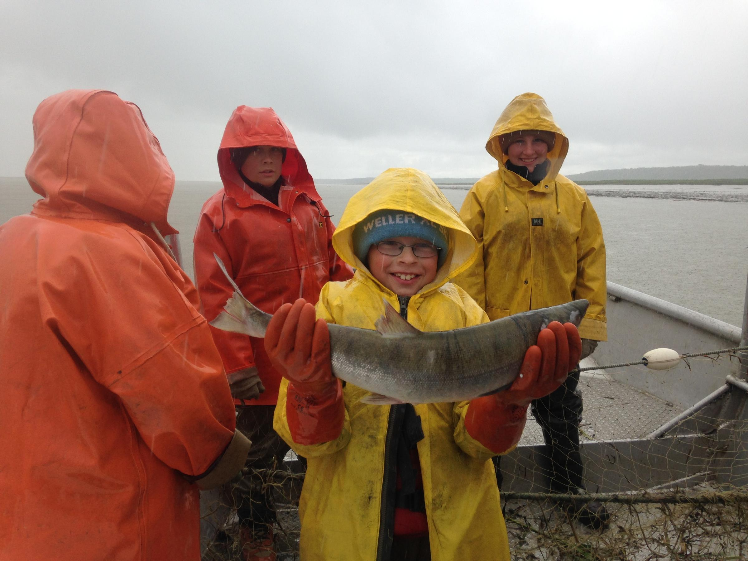 James Shawcroft holds up what might have been the 2 billionth commercially caught salmon in Bristol Bay's history at Coffee Point, July 6, 2016. (Photo by KDLG)