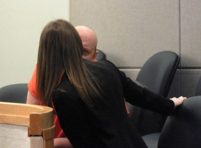 A defendant confers with his court-appointed defense attorney during an arraignment at the Dimond Courthouse in Juneau.