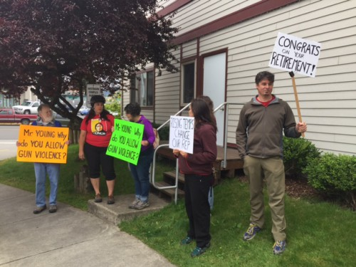 Protesters hold signs critical of Rep. Don Young while he spoke in Sitka. (Photo by Emily Kwong/KCAW)