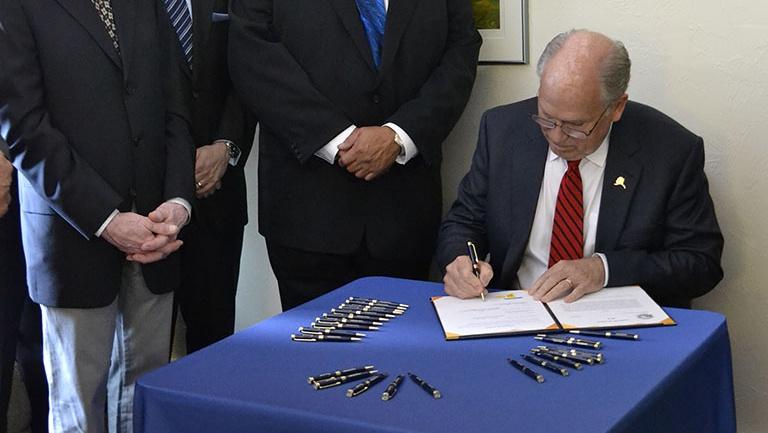 Gov. Bill Walker signs Senate Bill 91, a criminal justice reform bill, on July 11, 2016, at Haven House transitional housing in Juneau. (Photo courtesy Alaska Governor's Office)