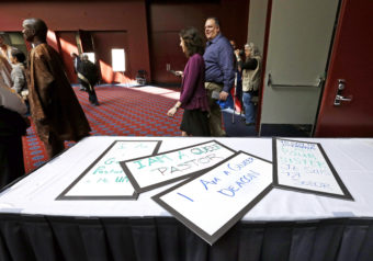 Attendees walk past a handful of placards during a break in the Methodists annual conference in Portland, Ore., in May 2016. The United Methodist Church, the nation's largest mainline Protestant denomination, was holding its once-every-four-years meeting and is facing a bitter fight over whether it should lift the church ban on same-sex marriage. Don Ryan/AP