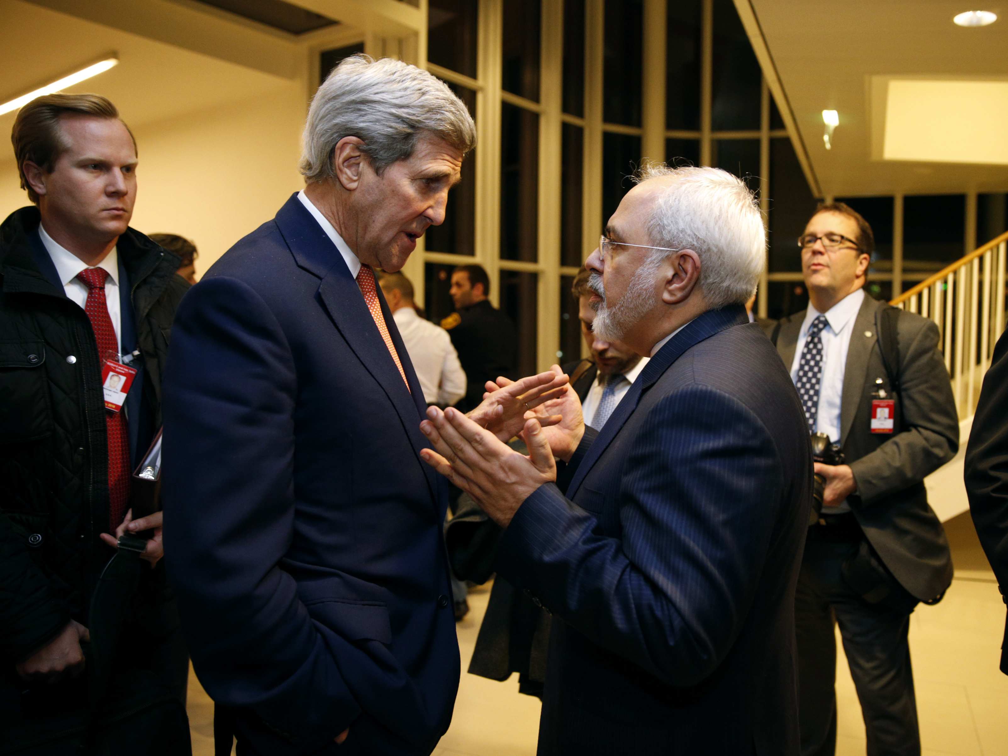 Secretary of State John Kerry talks with Iranian Foreign Minister Mohammad Javad Zarif in Vienna on Jan. 16, after the International Atomic Energy Agency verified that Iran met all conditions under the nuclear deal. The accord is now one-year-old. Iran is seen as abiding by the requirements of the deal, but its relations with the U.S. and other rivals have not improved on other fronts. (Photo by Kevin Lamarque/AP)