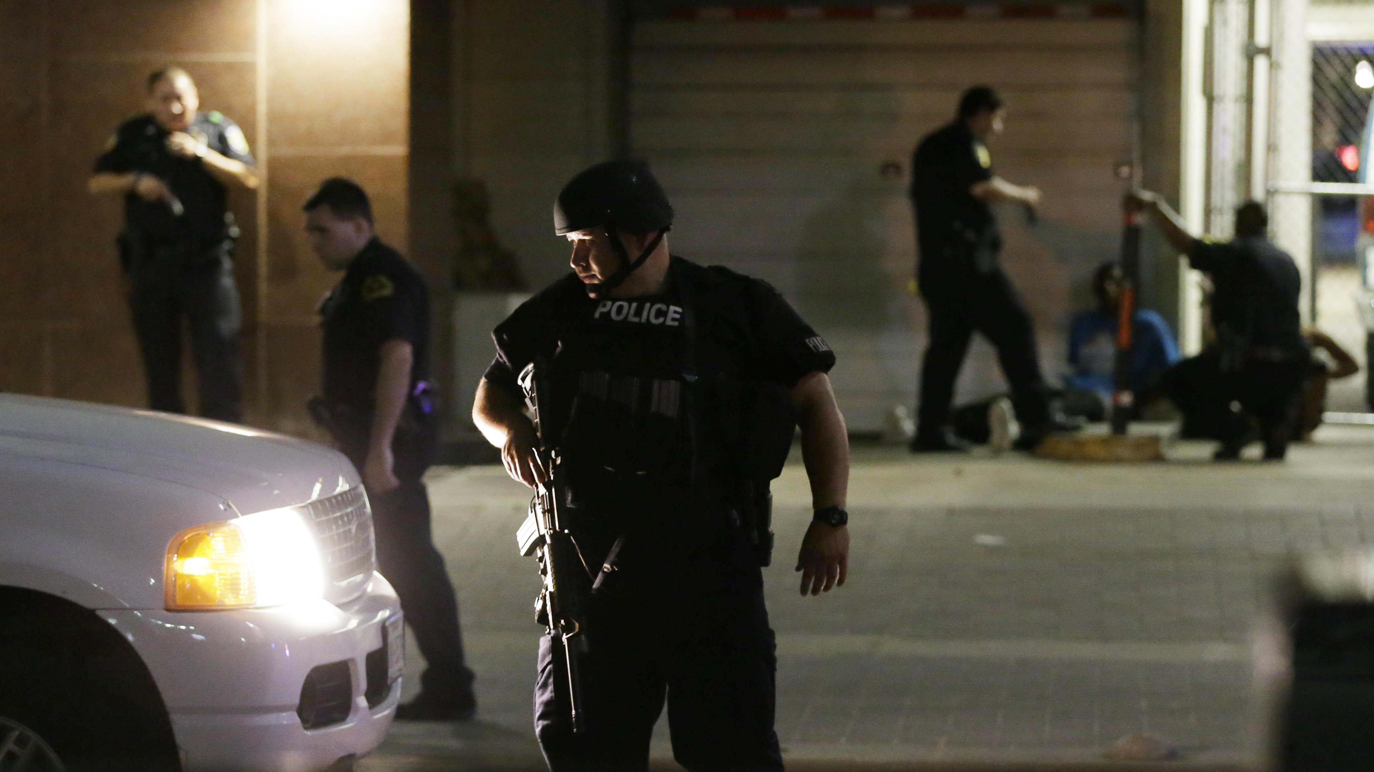 Dallas police detain a driver after several police officers were shot Thursday evening in downtown Dallas. Snipers shot police officers — killing several — during a peaceful protest, the city's police chief said at a news conference. (Photo by L.M. Otero/AP)