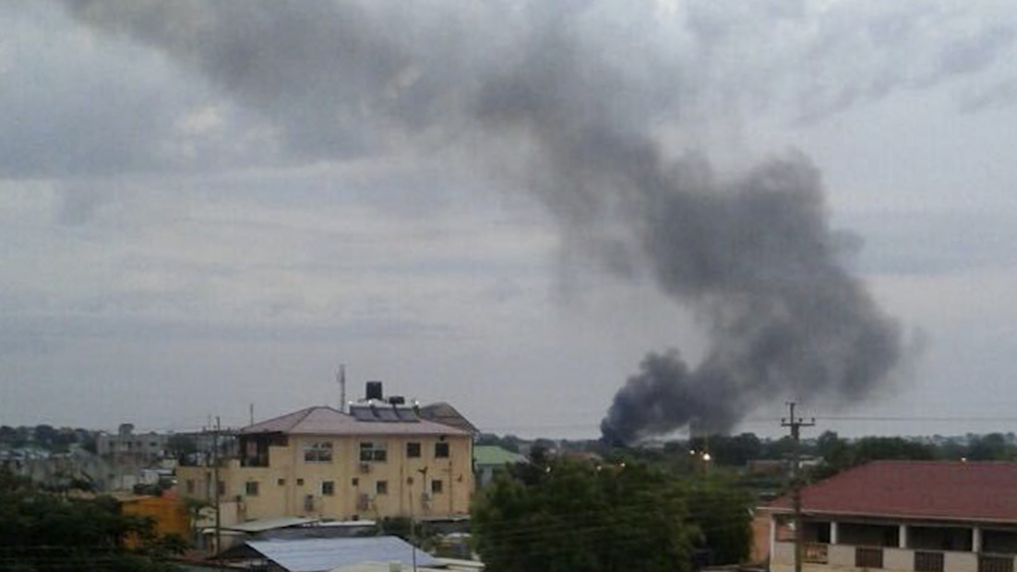 Black smoke rises above Juba, the capital of South Sudan, on Sunday. Explosions and heavy weapons gunfire are shaking Juba Monday in the fifth day of clashes between government and opposition forces, raising the specter of a return to civil war. (Iain McLellan/AP)