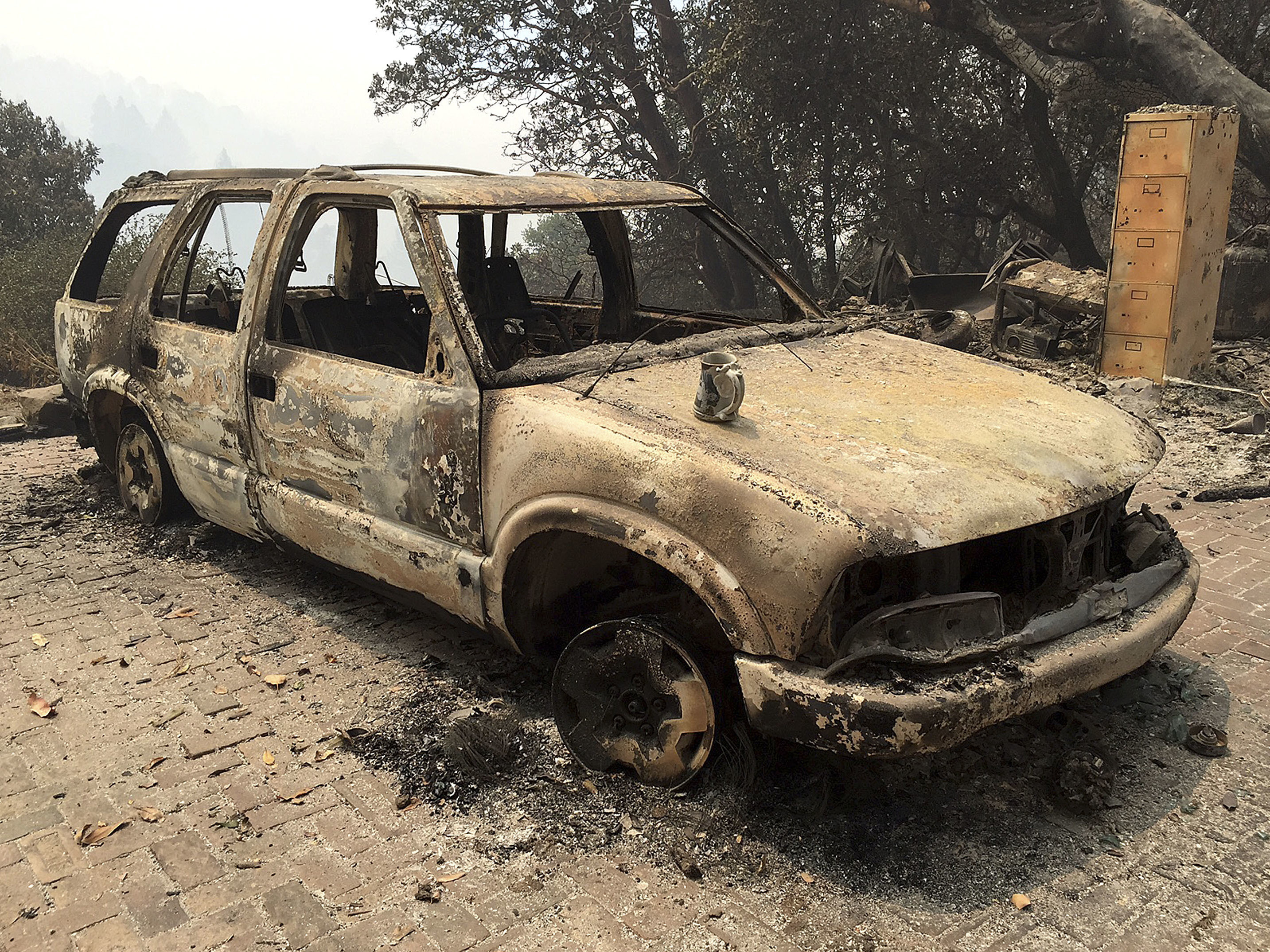 A car destroyed by the Soberanes fire in Big Sur, Calif. Lodge managers and cafe owners there are facing cancelled bookings after fire officials warned that crews will likely be battling the fire for another month. Terry Chea/AP