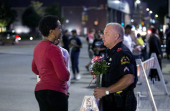 A woman speaks with an officer at a vigil outside Dallas police headquarters in Dallas on Friday. Bilgin Sasmaz/Anadolu Agency via Getty Images
