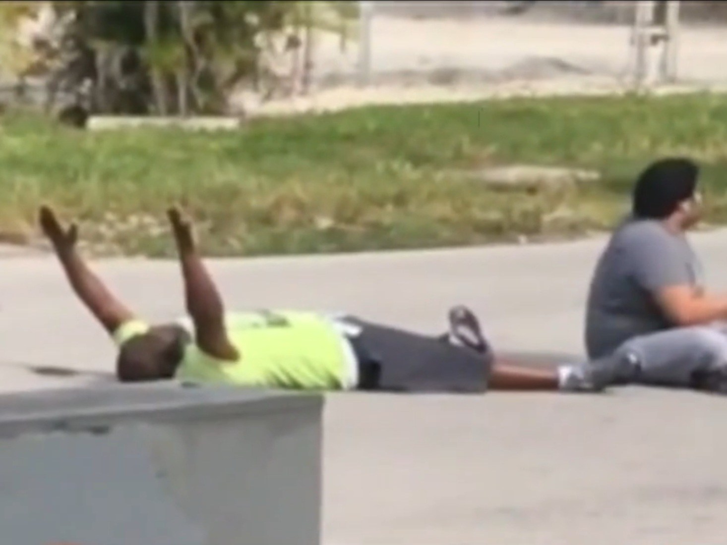 In a video filmed on Monday, Charles Kinsey (left) lies next to the autistic patient he was trying to help, holding his hands up in an effort to assure the North Miami police that they aren't a threat. Kinsey was later shot in the leg by the police. (Photo by Channel 7 WSVN/Screenshot by NPR)