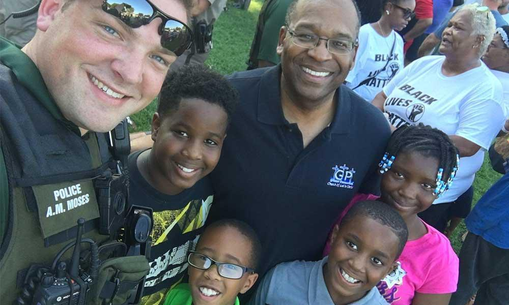 A Wichita police officer poses with residents at the First Steps Community Cookout on Sunday. (Photo courtesy Wichita Police)