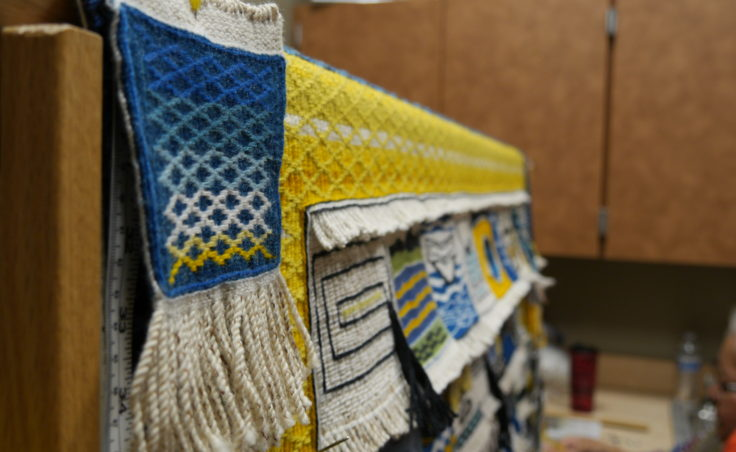 Teahonna James square is tacked to the loom at the Sealaska Heritage Institute, Juneau. James' design inspired the pattern and colors of the Weavers Across Waters Chilkat/Ravenstail community robe. (Photo by Tripp J Crouse/KTOO)