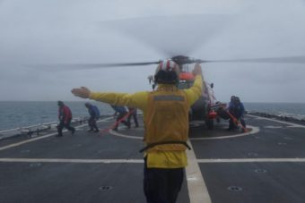 A member of the Stratton's crew signals to the pilot of a Coast Guard helicopter during a training exercise held earlier this month off Alaska's northern coast. The agency has stationed two MH-60 helicopters in Kotzebue to help it respond more quickly to emergencies around the remote Arctic expanse. (Photo by Gina Caylor, U.S. Coast Guard)
