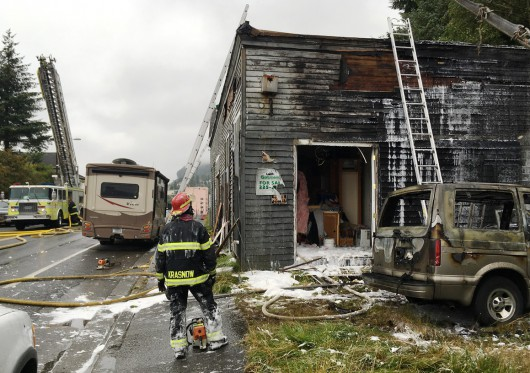 Firefighter Seth Krasnow watches the progress of fire crews as they make sure hot spots are extinguished in a Stedman Street building that caught fire Wednesday. (Leila Kheiry, KHNS)
