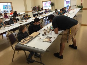 Ron Fairbanks teaching kids how to paint formline. (Aaron Bolton, KSTK)