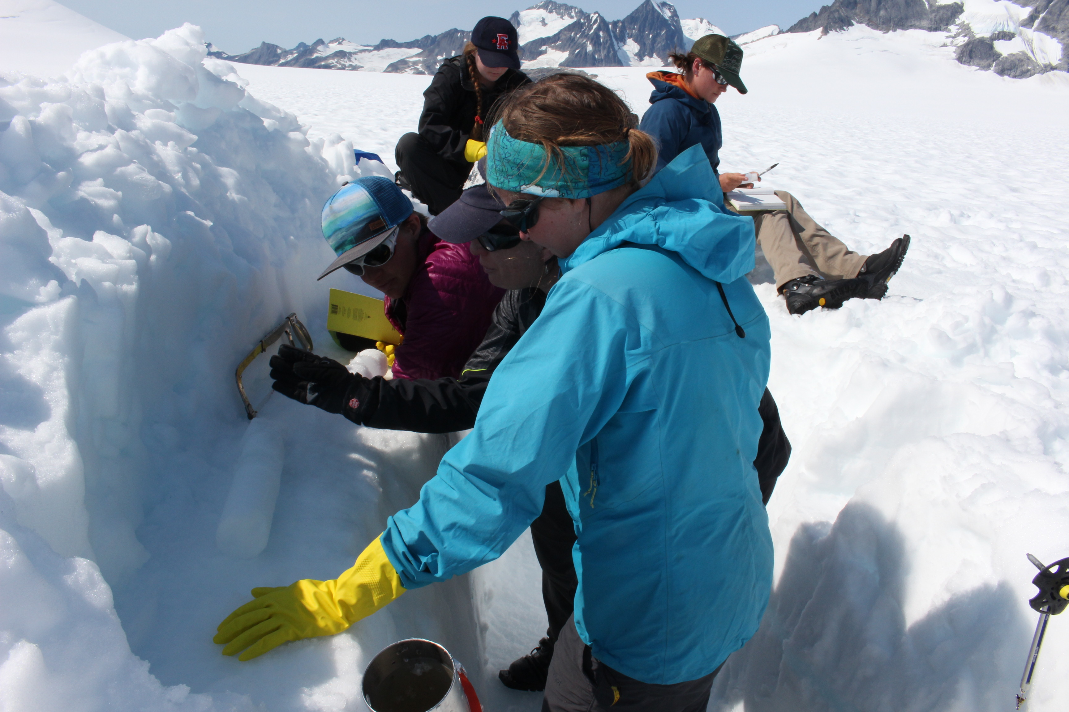 Natalie Kehrwald leads a group of Juneau Icefield Program students on how to saw an ice core. (Photo by Elizabeth Jenkins/KTOO)
