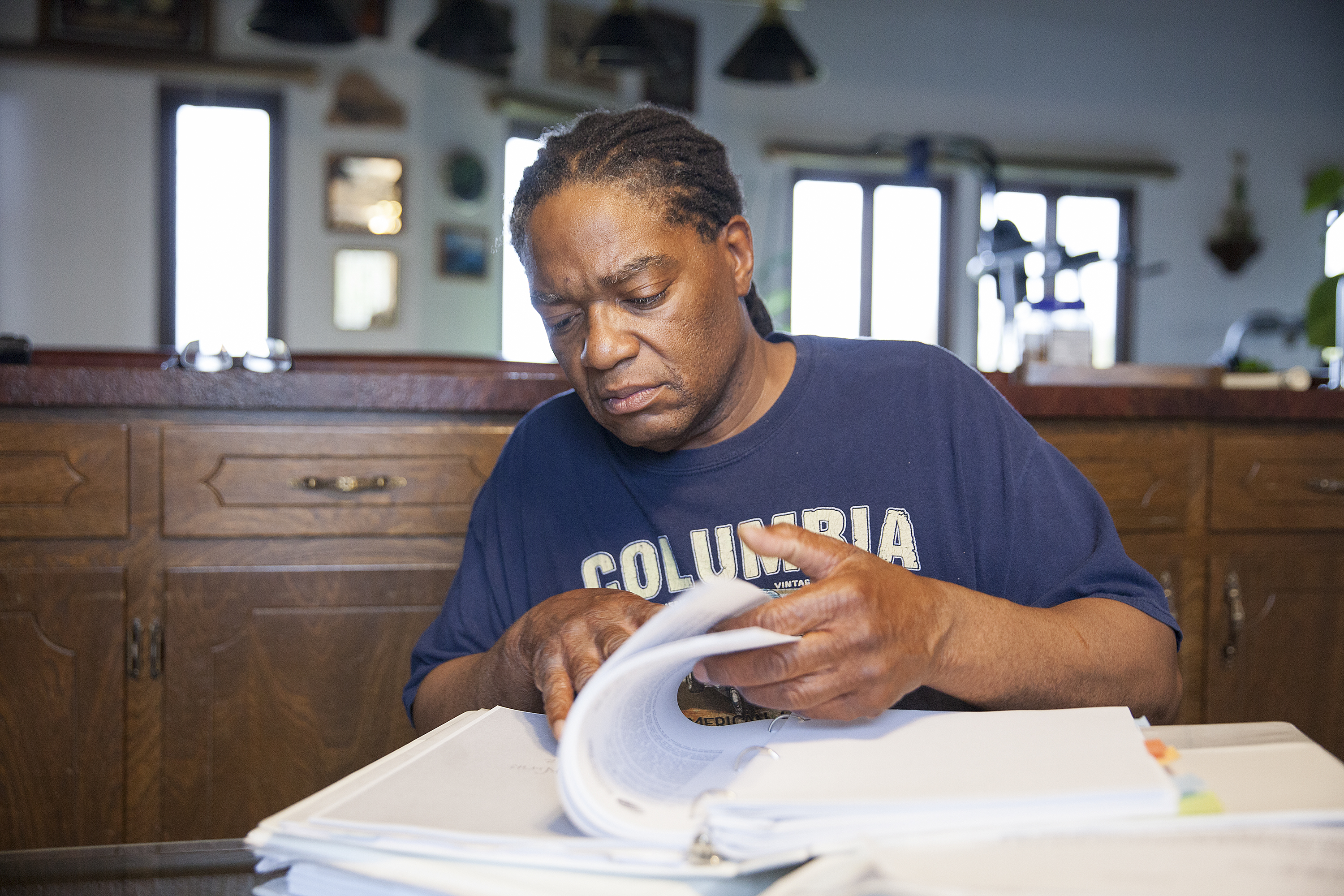 "Theodore ""Teddy"" Burns looks through documents from his discrimination case at his home in Anchorage. Burns' appeal with the Ombudsman Office took eight years to complete. (Photo by Rashah McChesney/ KTOO)"