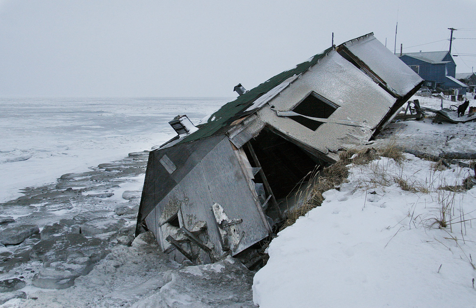 An abandoned house at the west end of Shishmaref, Alaska, sits on the beach after sliding off during a fall storm in 2005. (Photo by Diana Haecker/Associated Press)