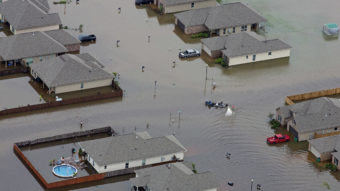 In this aerial photo a boat motors between flooded homes on Saturday after heavy rains in the region in Hammond, La. Max Becherer/AP