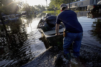Daniel Stover, 17, moves a boat of personal belongings from a friend's flooded home in Sorrento, La., on Saturday. Max Becherer/AP