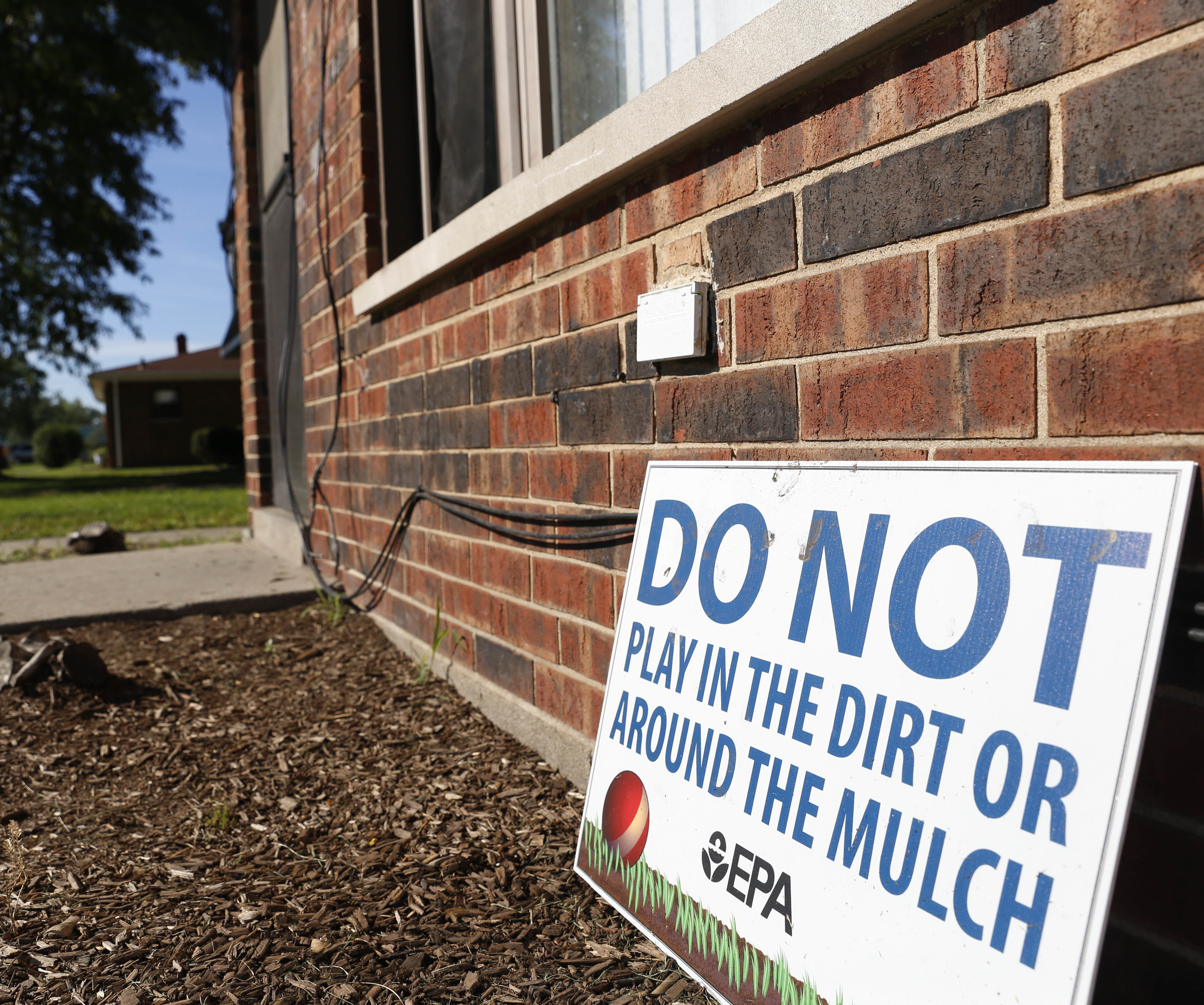 A sign from the Environmental Protection Agency posted in front of West Calumet Housing Complex houses in East Chicago, Ind. (Photo by Tae-Gyun Kim/Associated Press)