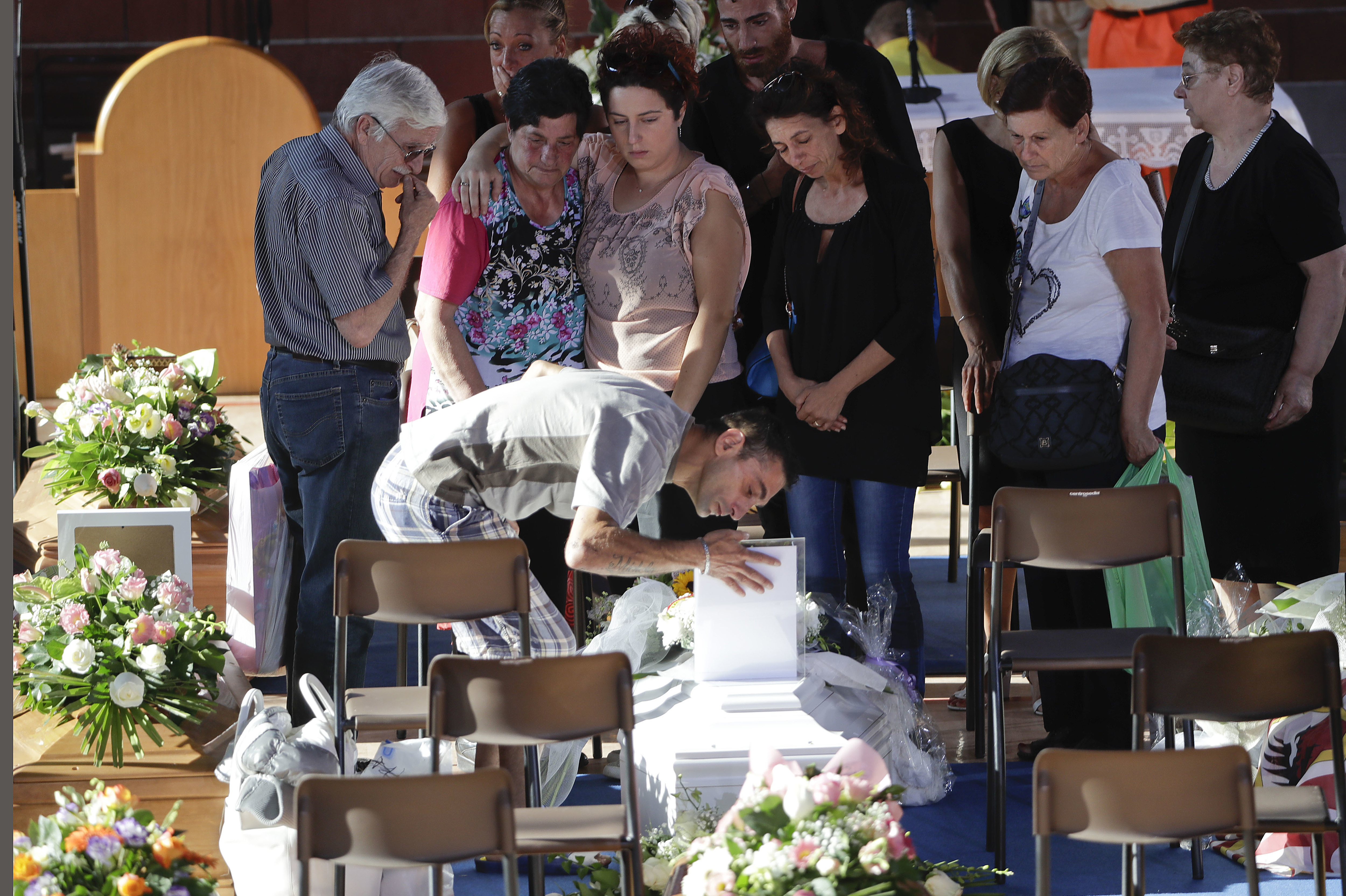 Relatives mourn over a coffin of one of the earthquake victims prior to the start of the funeral service on Saturday in Ascoli Piceno, Italy. Gregorio Borgia/AP