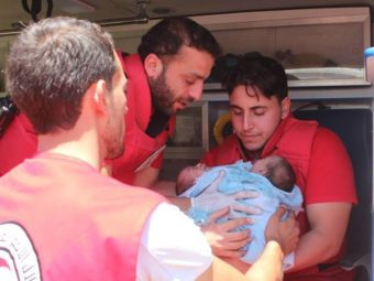 A Syrian Red Crescent team works to evacuate the conjoined twins to a hospital in Damascus on Friday. Courtesy of the Syrian American Medical Society
