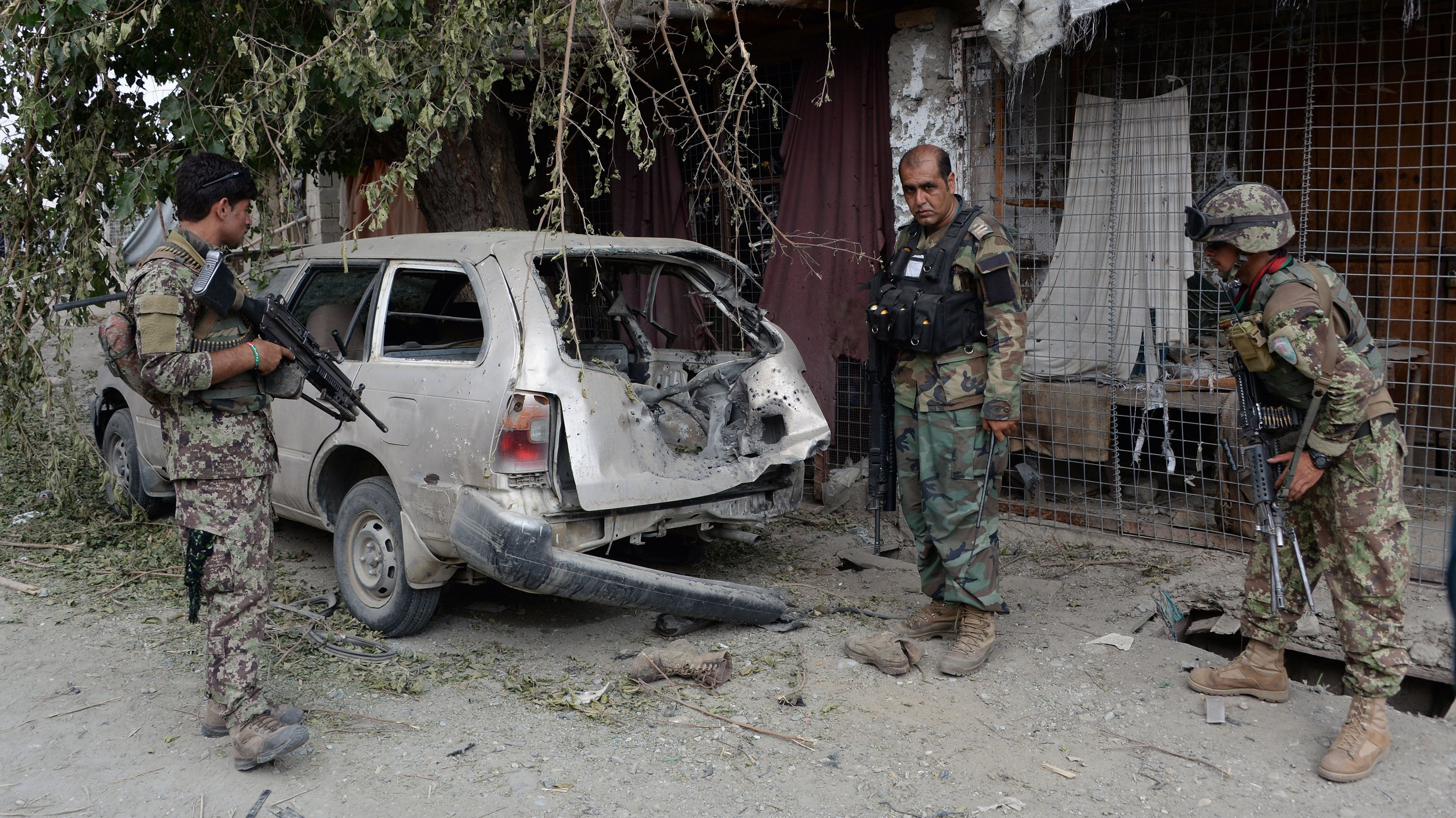 Afghan soldiers inspect a destroyed vehicle after an operation in Nangarhar province, Afghanistan, on July 26, the day the Pentagon says a drone strike killed the leader of the Islamic State in the region. Noorullah Shirzada/AFP/Getty Images