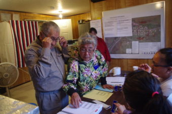 Anecia Toyukak helps her husband, Mike, look at the ballots in Manokotak on Aug. 16, 2016. (Photo by Molly Dischner/KDLG)