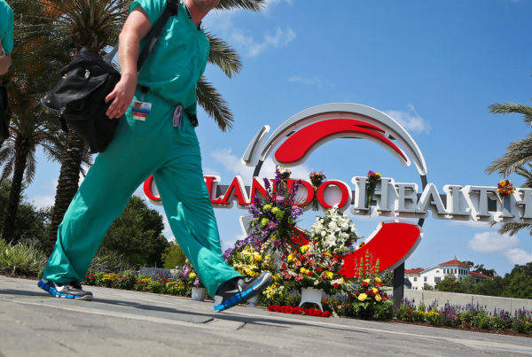 Medical professionals walk by a makeshift memorial set up at the Orlando Health sign in June in Orlando, Fla. (Photo by Jacob Langston/Orlando Sentinel/TNS via Getty Images)