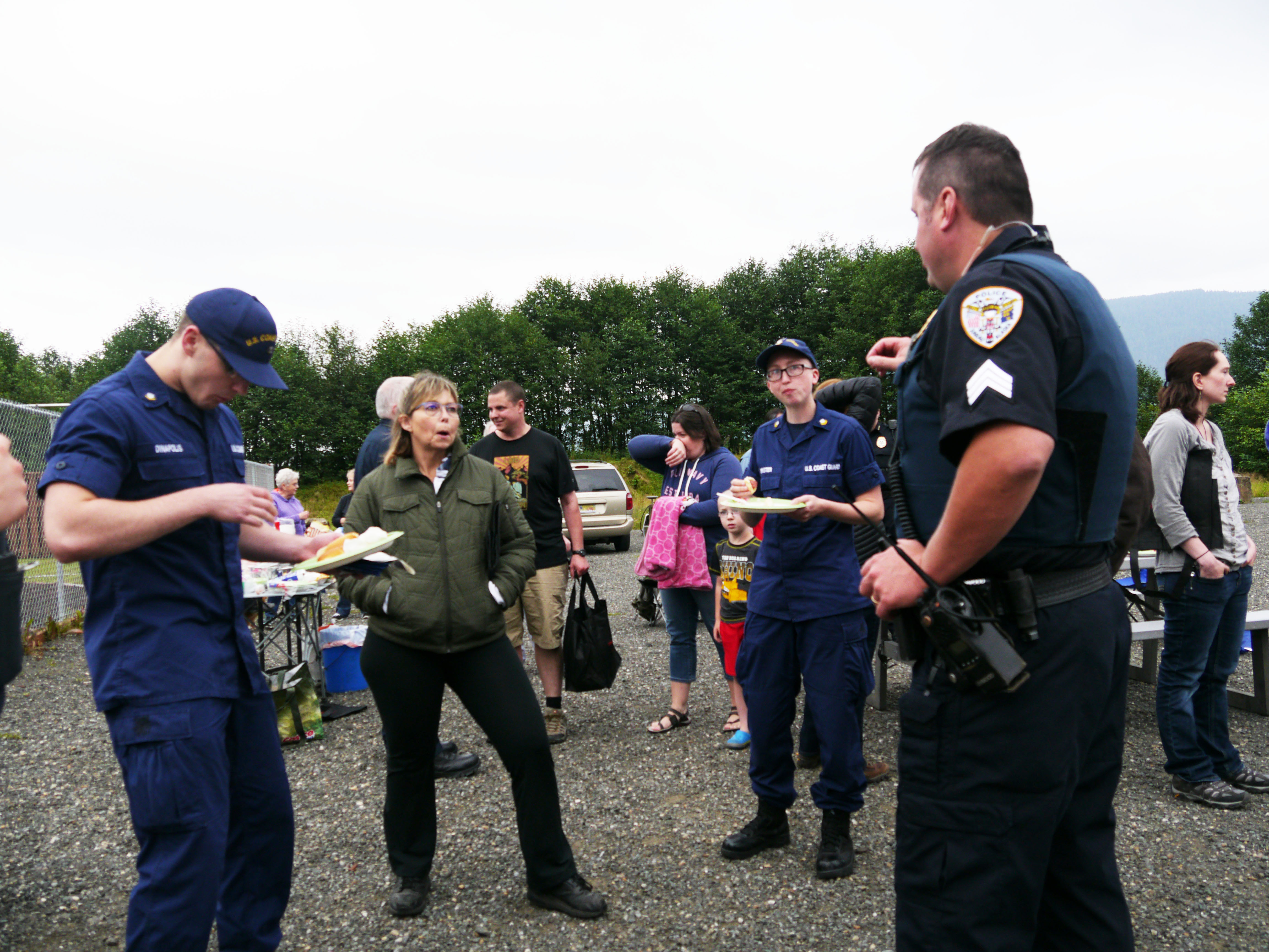 Juneau Police Department Sgt. Chris Gifford speaks with a two Coast Guard members and a community member during National Night Out, Aug. 2, 2016. (Photo by Lakeidra Chavis/ KTOO)