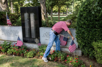 Russell Mercer replaces old U.S. flags with new ones at the Flushing World Trade Center Memorial at Flushing Cemetery in New York City. His stepson, Scott Kopytko, was killed on Sept. 11. Alex Welsh for NPR