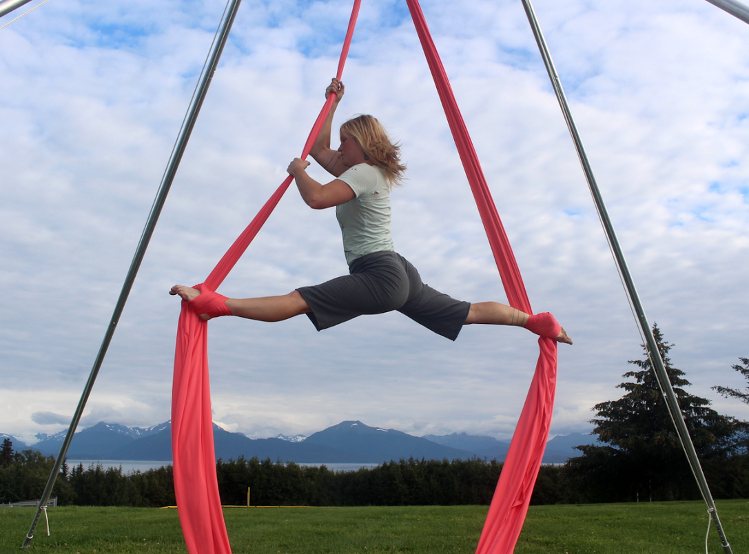 Instructor Bridget Doran practicing aerial silk art above Kachemak Bay. (Photo courtesy of Kammi Matson)