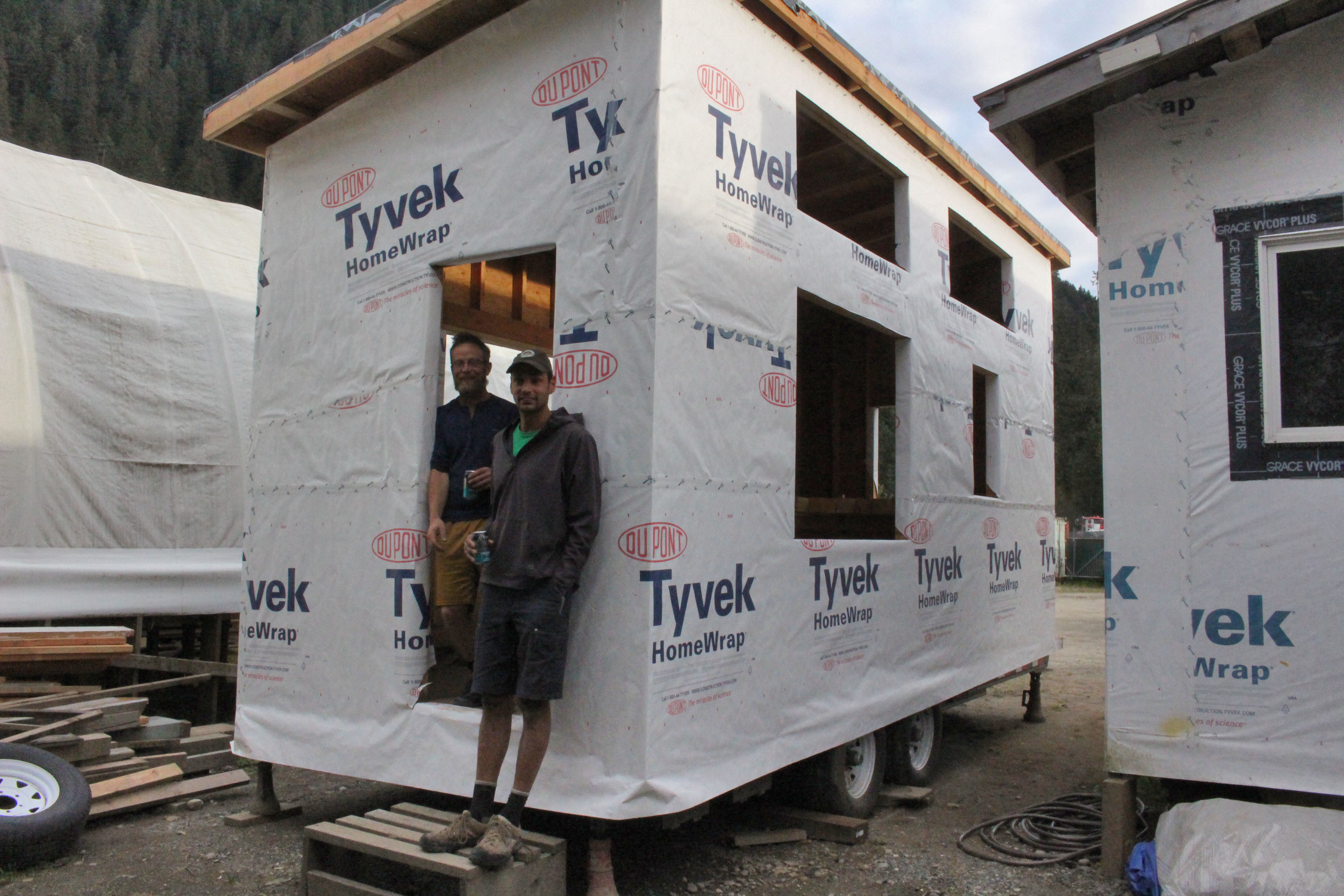 Jason Donig (right) and Jeff Martinson (left) stand in front of the tiny they're building. (Photo by Elizabeth Jenkins/KTOO)