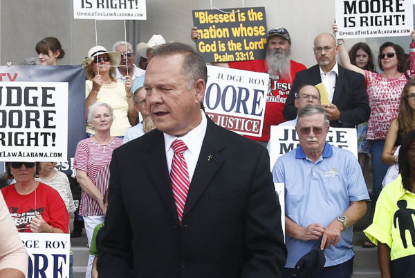 Alabama Chief Justice Roy Moore, seen here addressing the media in August, won't be paid for the rest of his term and must pay court costs. (Photo by Brynn Anderson/Associated Press)