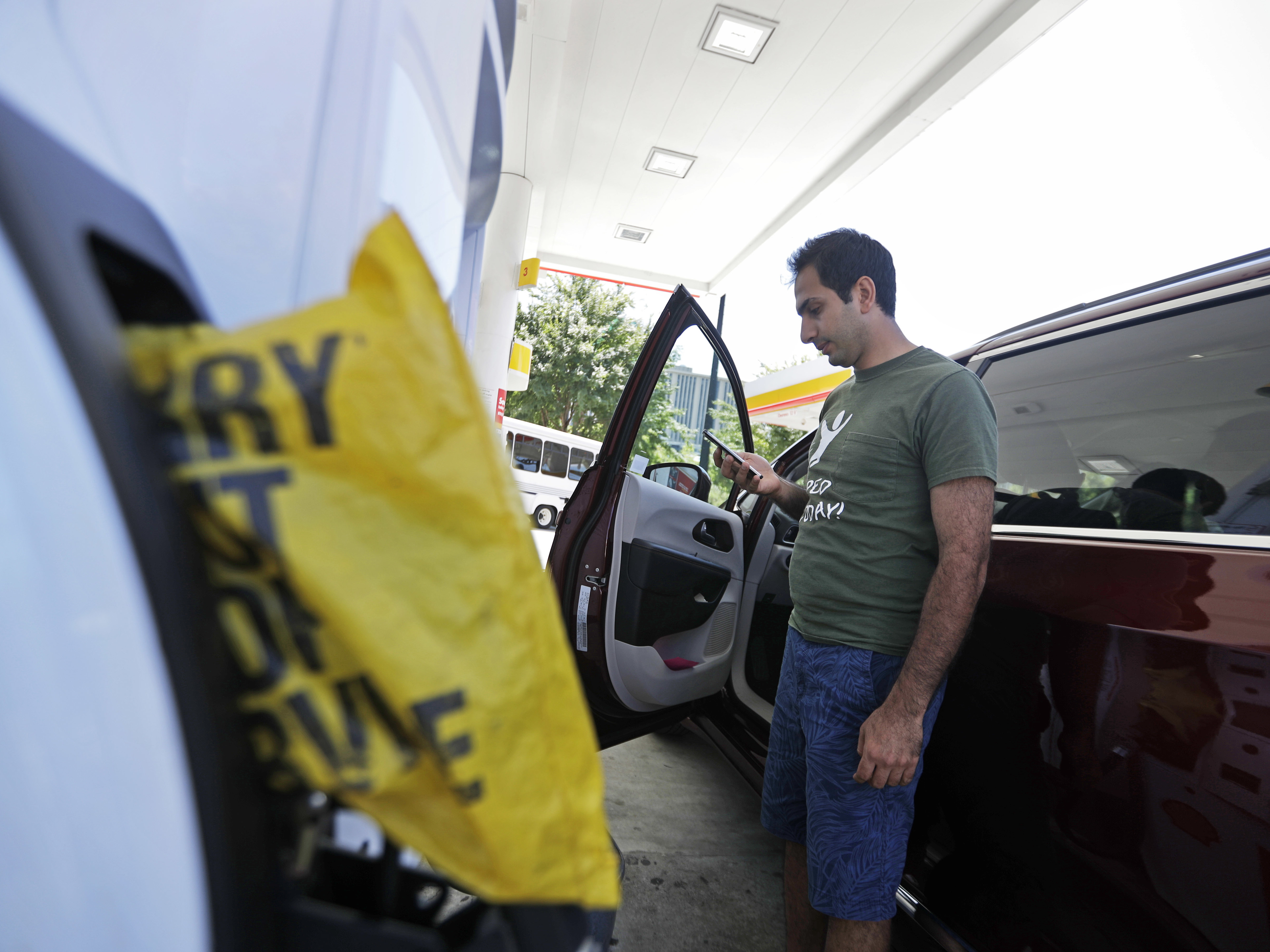 "A motorist who found an Atlanta gas station had run out of fuel calls a nearby gas station Monday to see if they have any left. Gas prices spiked and drivers found ""out of service"" bags covering pumps as the gas shortage in the South rolled into the work week, raising fears that the disruptions could become more widespread. (Photo by David Goldman/Associated Press)"