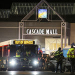 Emergency personnel stand in front of an entrance to the Cascade Mall at the scene of a shooting where five people were killed on Friday in Burlington, Wash. Stephen Brashear/AP