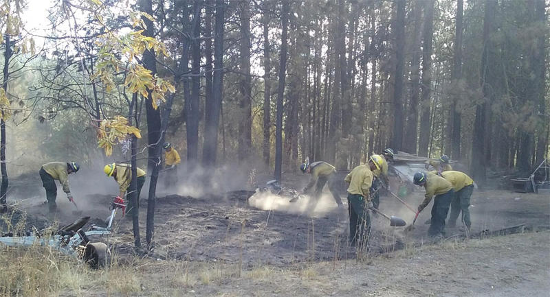 Firefighters mop up remaining fire and heat near residences threatened by the Cayuse Mountain Fire. (INCIWEB)