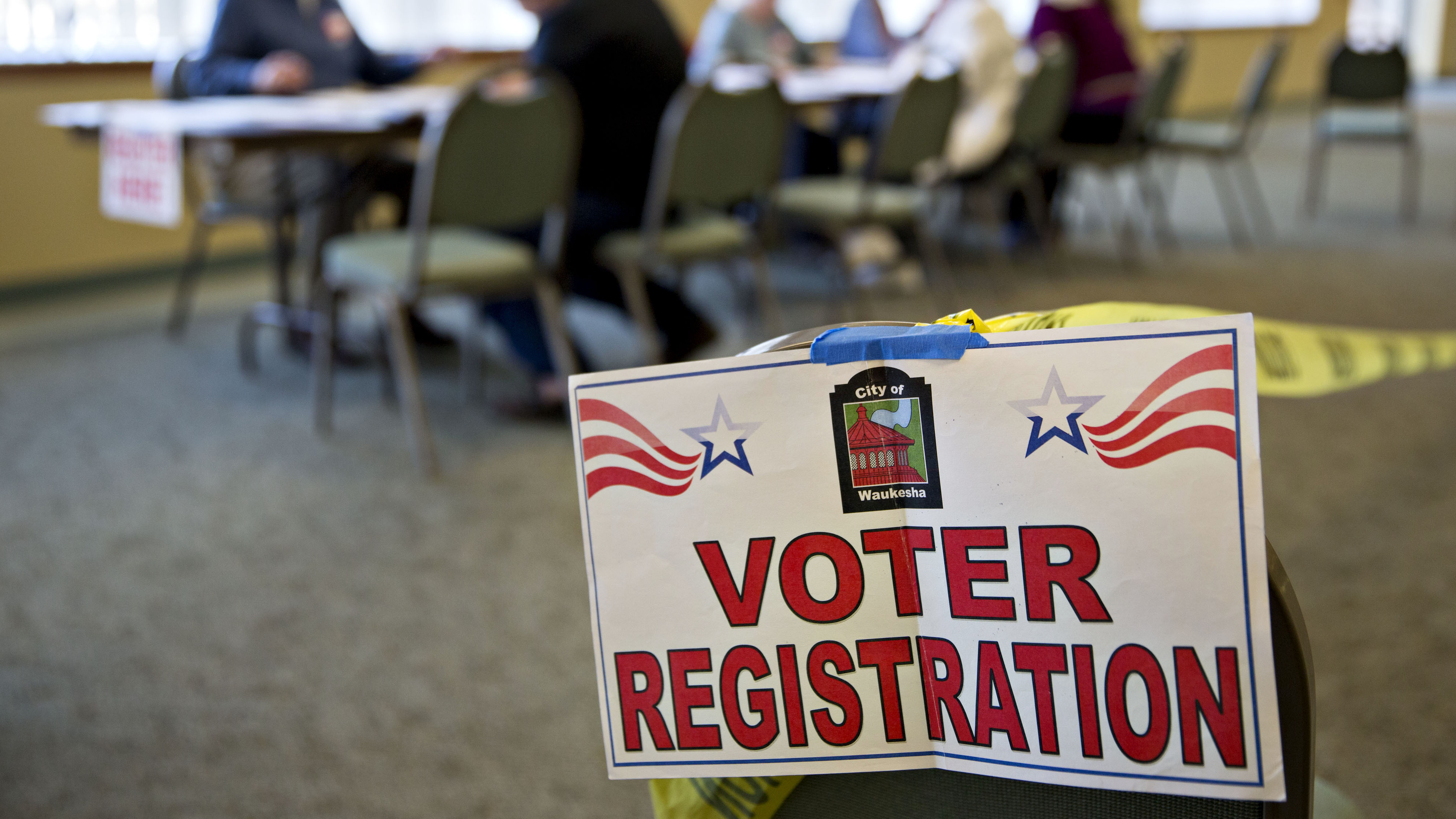 A voter registration sign hangs near a table where residents fill out paperwork at a polling location during the presidential primary vote in Waukesha, Wis., on April 5. (Photo by Daniel Acker/Bloomberg via Getty Images)