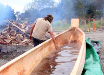 Tommy Joseph feels the warm water after the batch of lava rocks are taken out. (Photo by Emily Russell/KCAW )