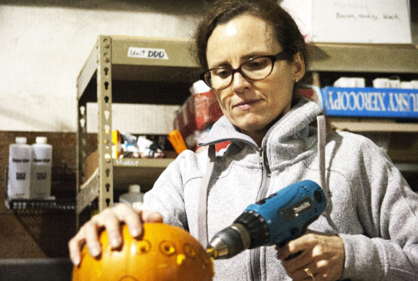 Amy Karpstein uses a drill to carve small holes into her pumpkin at Juneau Makerspace in Lemon Creek on Monday, October 24, 2016. Karpstein was one of seven people using the space Monday night during an open studio night. (Photo by Tripp J Crouse/KTOO)