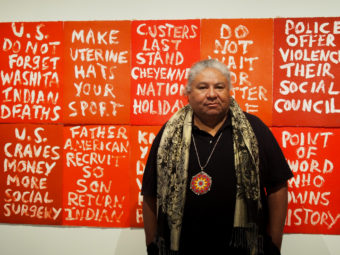 "Artist Edgar Heap of Birds stands before his piece ""Dead Indian Stories"" on display in the ""Without Boundaries"" exhibit. (Photo by Zachariah Hughes/Alaska Public Media)"