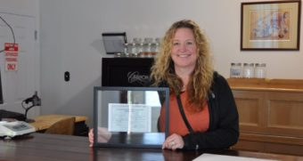Tara Bass with in the Remedy Shoppe with her license to open.