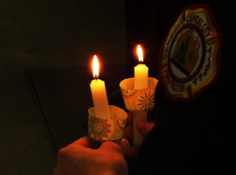 Candles are lit as Juneau firefighters read the names of other firefighters who died last year.
