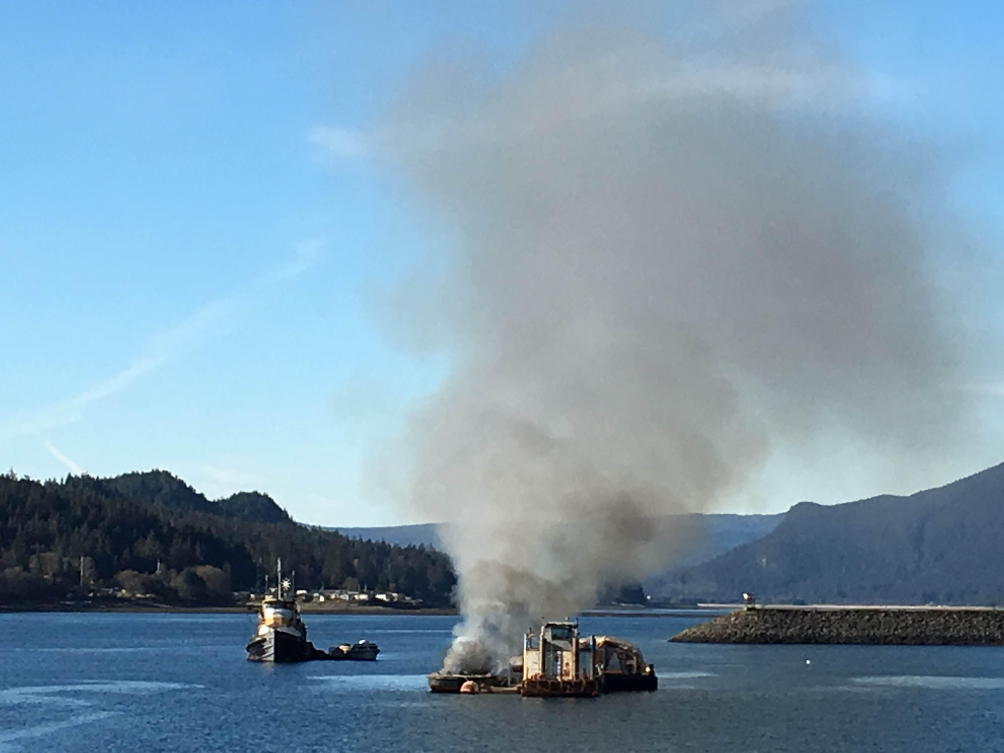 A small barge burns near Aurora Harbor along Egan Drive. (Lakeidra Chavis/ KTOO)