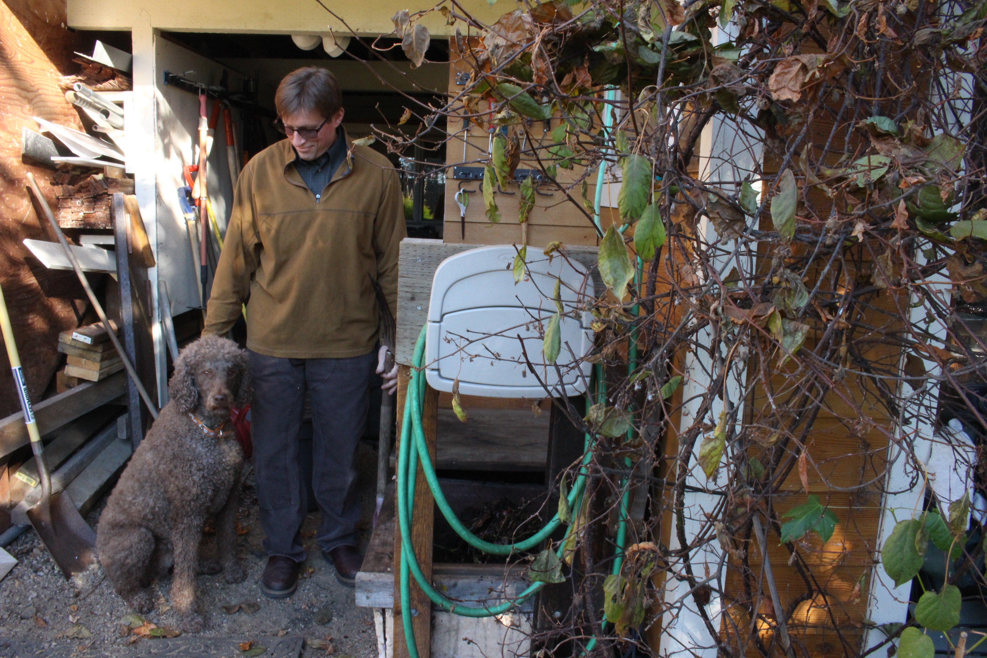 Bob Deering at his home with his dog Gamby and compost bins. (Photo by Elizabeth Jenkins/KTOO)