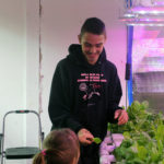 Dallas Roberts shares lettuce from St. Pauls's greenhouse with students. (Photo by Zoë Sobel/KUCB)